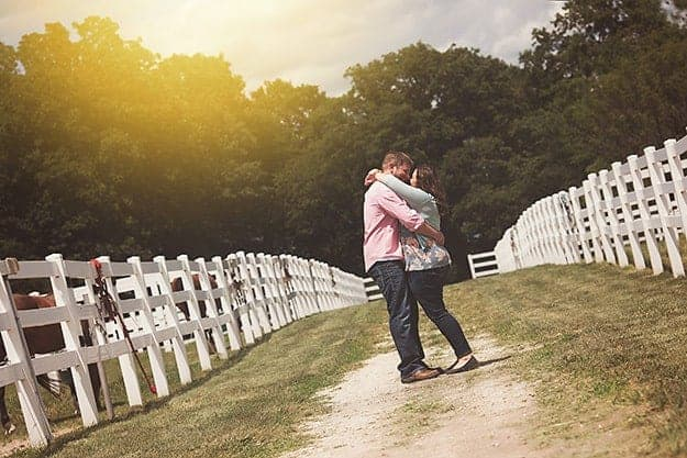 Karly and her husband hugging on a dirt road.