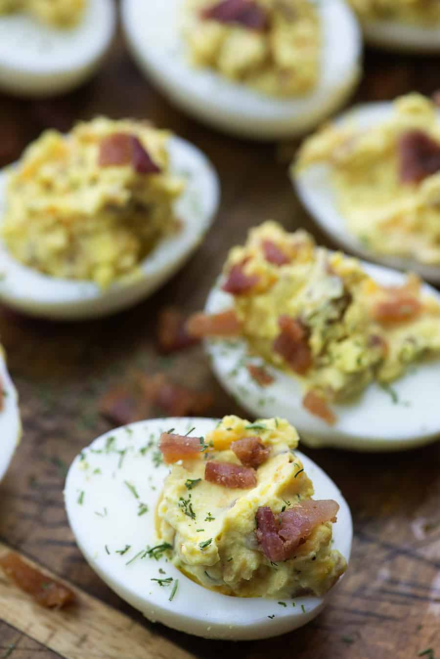 keto deviled eggs on wooden cutting board with bacon