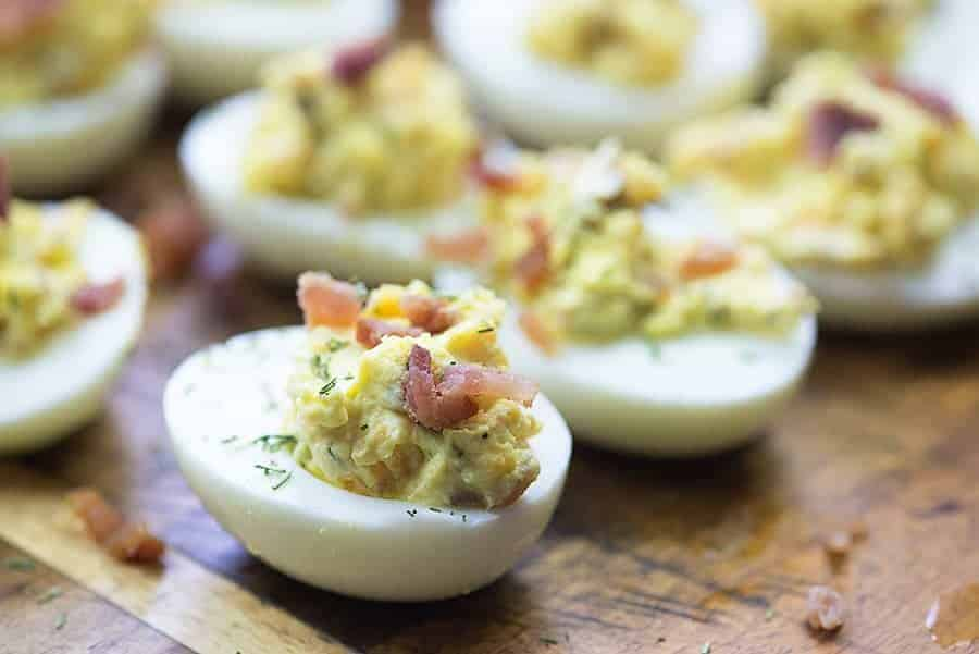 deviled egg recipe with bacon on cutting board