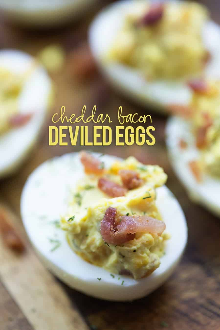 deviled eggs with bacon on cutting board