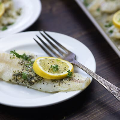 baked cod with butter and lemon on a white plate