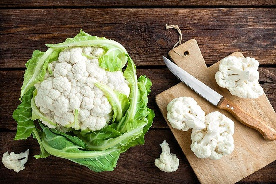 cutting cauliflower wooden background