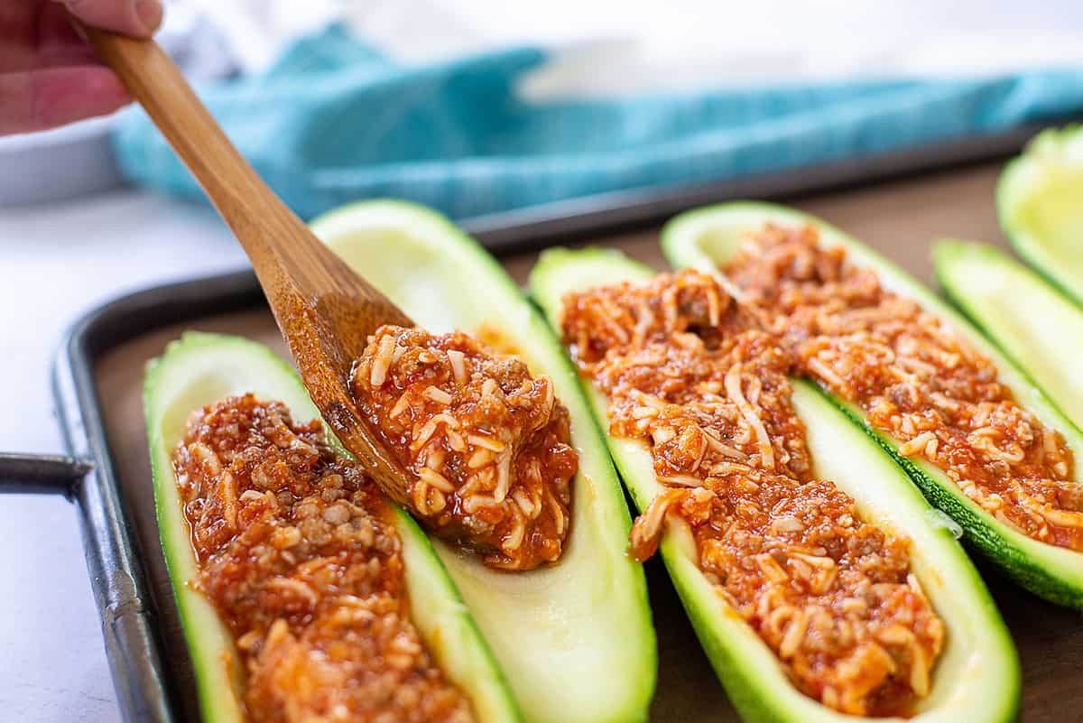 person filling zucchini boats with sauce.