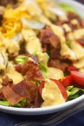 Closeup of salad topped with bacon and thousand island dressing