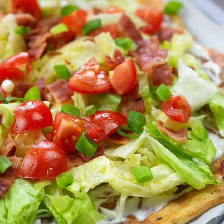 pizza crust with cheese, lettuce and tomatoes on top