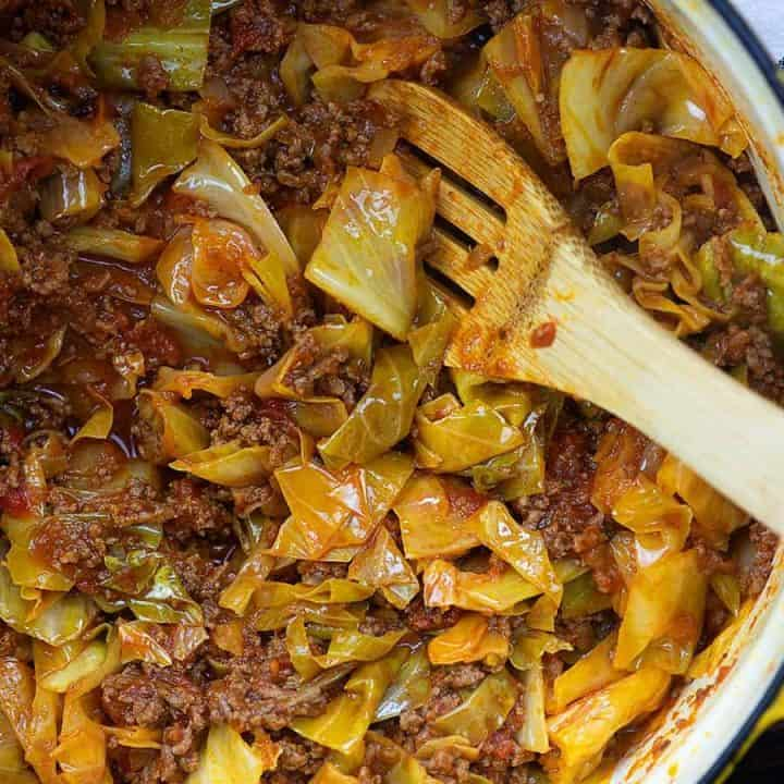 cabbage and sausage in a dutch oven with a wooden spoon stirring it