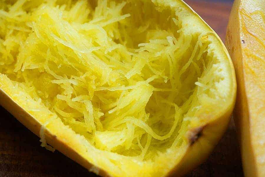 shredded squash in a squash that has been sliced in half