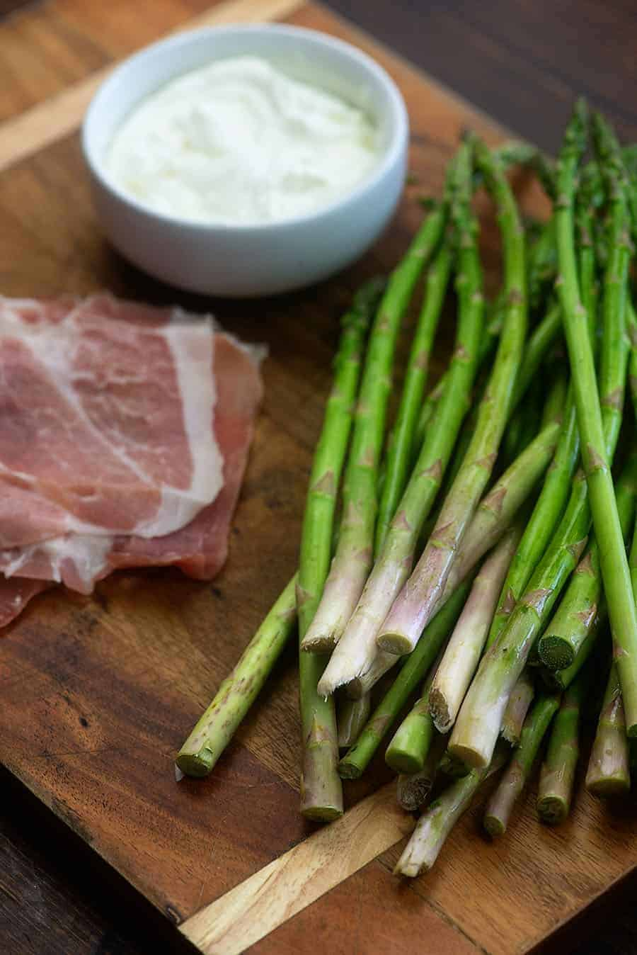 ingredients for prosciutto wrapped asparagus on wooden cutting board