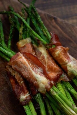 several asparagus each wrapped in prosciutto on top of a dark cutting board