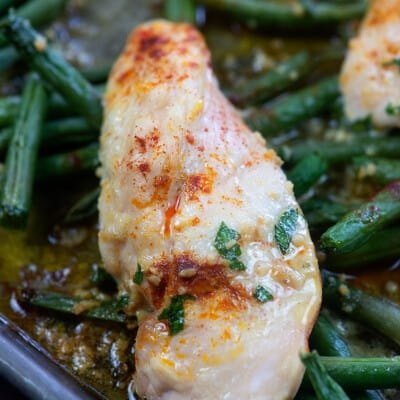 cooked chicken and green beans on a baking sheet