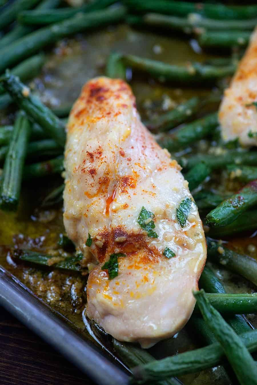 chicken breast on green beans in a cookie sheet