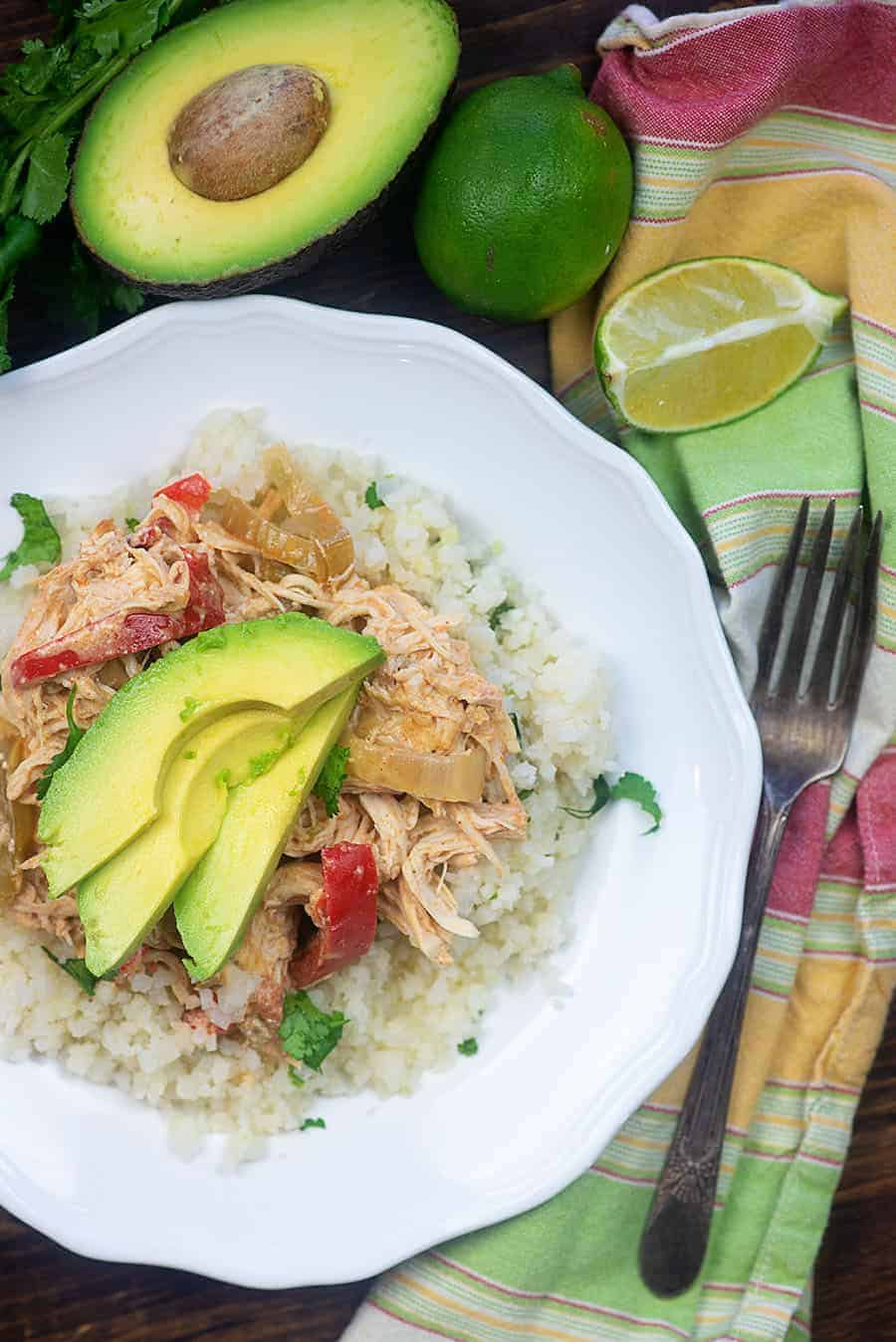 chicken fajitas topped with avocado slices on a white plate with colorful cloth napkin
