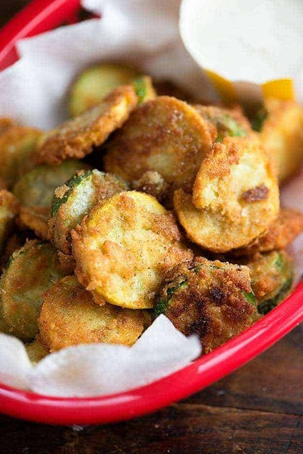 Fried zucchini piled up in a clear glass pie pan