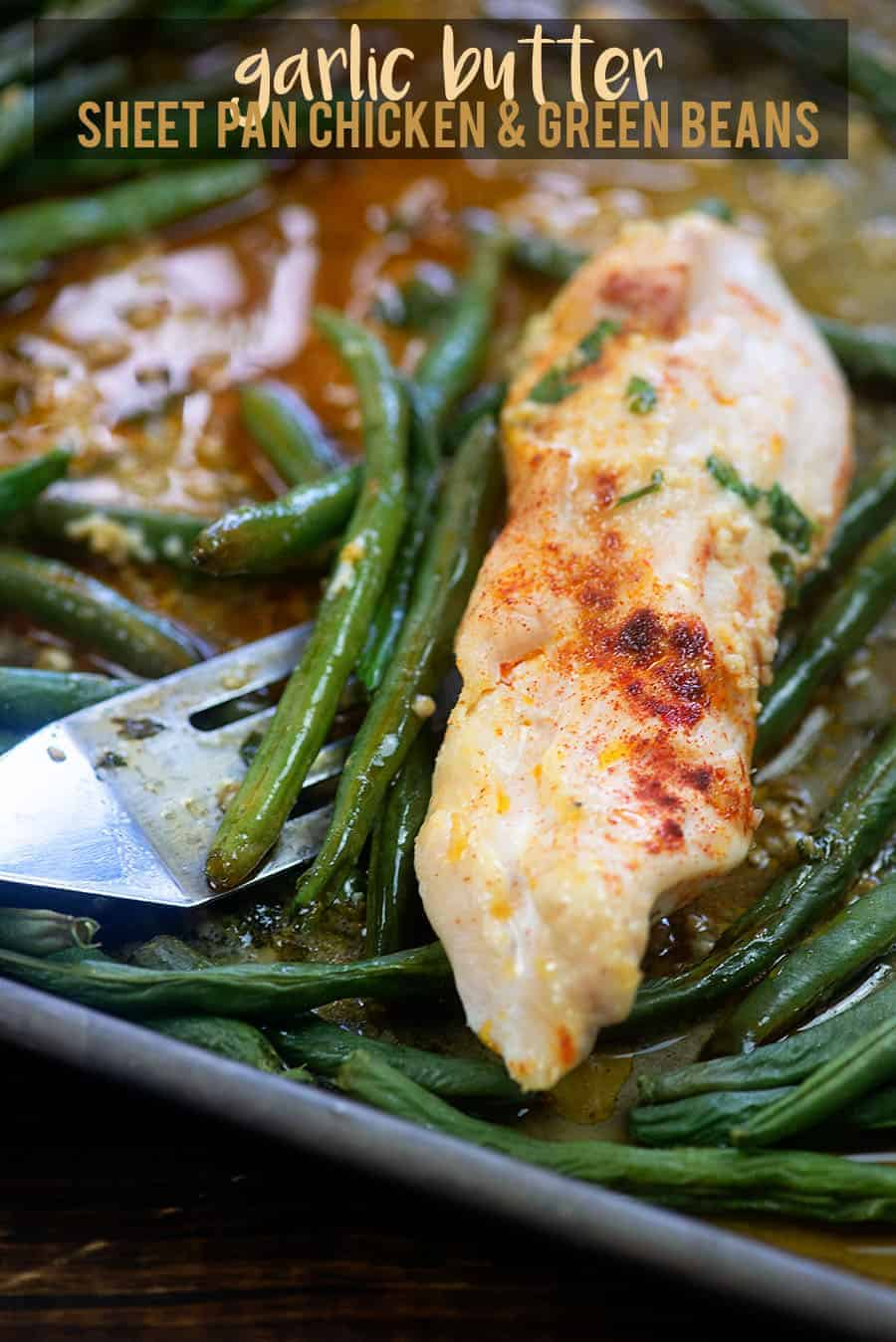 garlic butter chicken and green beans getting scooped off a baking sheet