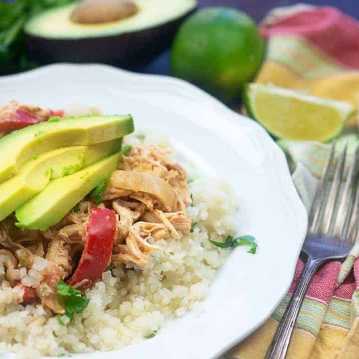 diced cauliflower, chicken, and avocado slices on a small white plate