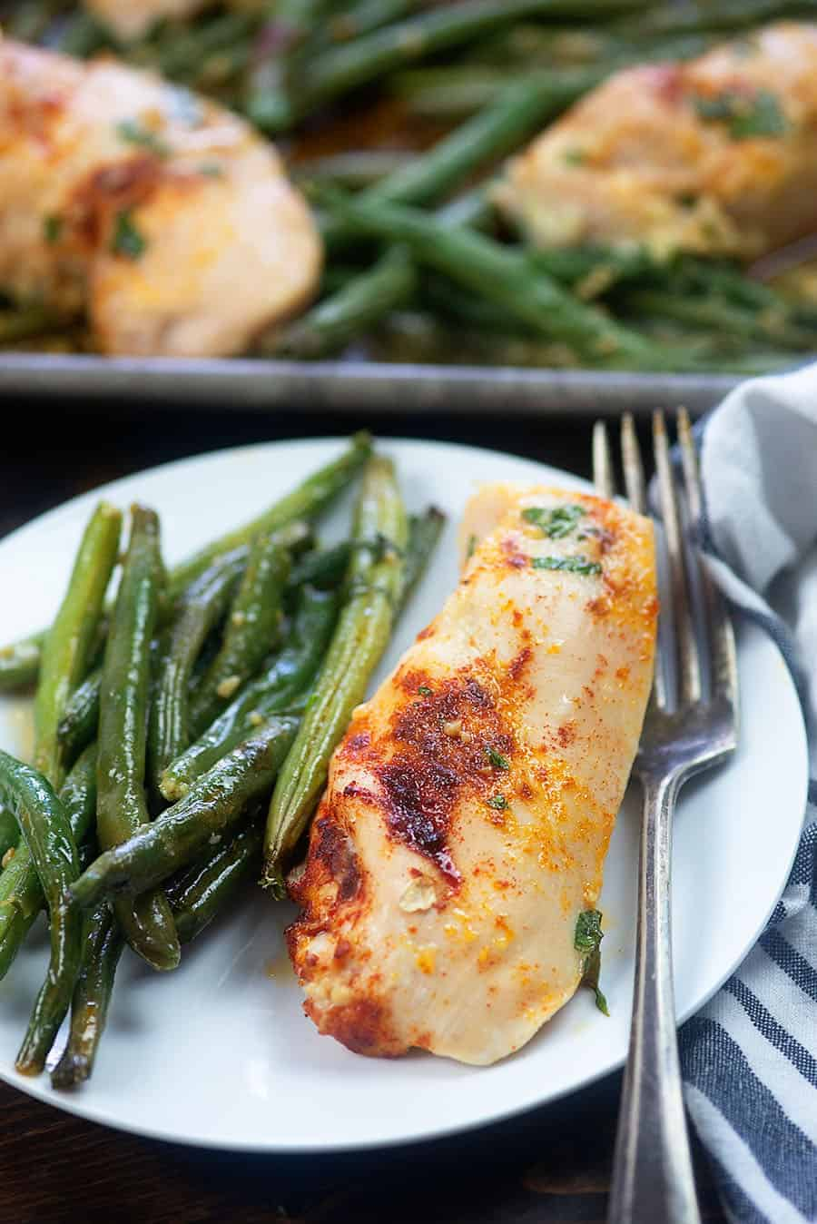 chicken and green beans on a white plate with fork and dish towel