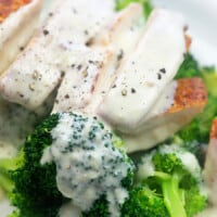 A close up of a plate of food with broccoli, with Alfredo sauce and Chicken
