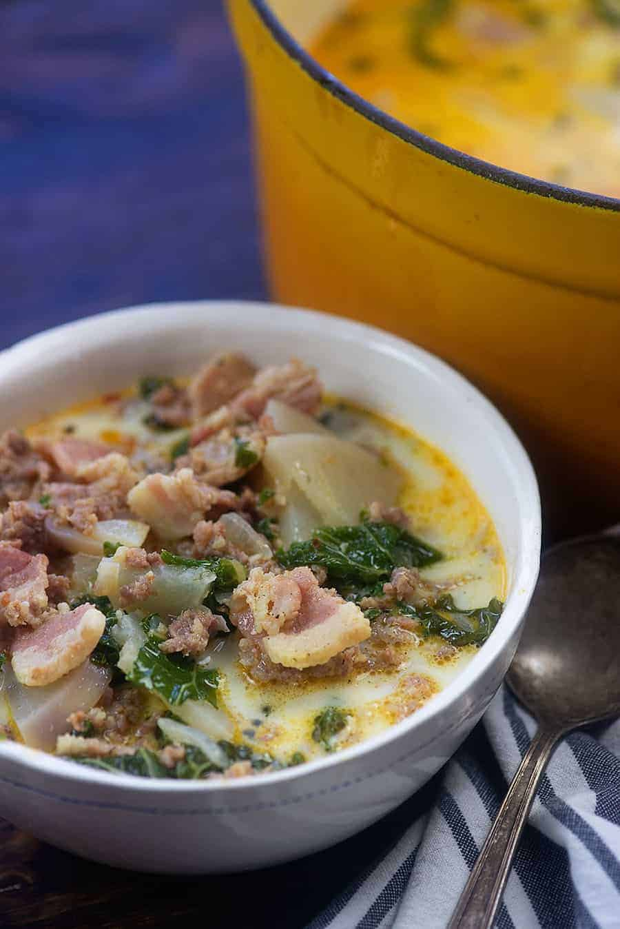bowl of zuppa toscana next to a pot