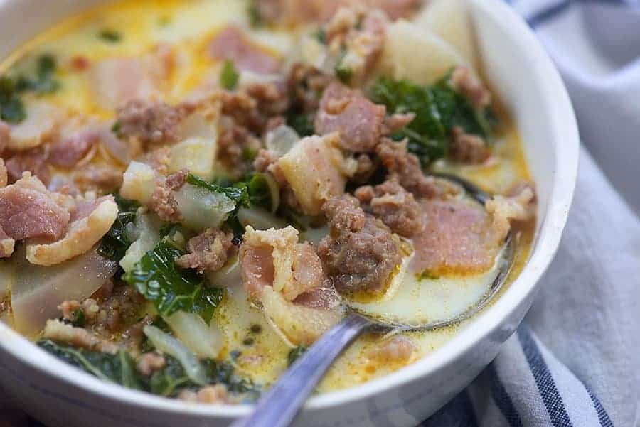 bowl of zuppa toscana with a spoon it