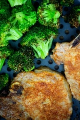 A plate of food with broccoli, with Pork chop