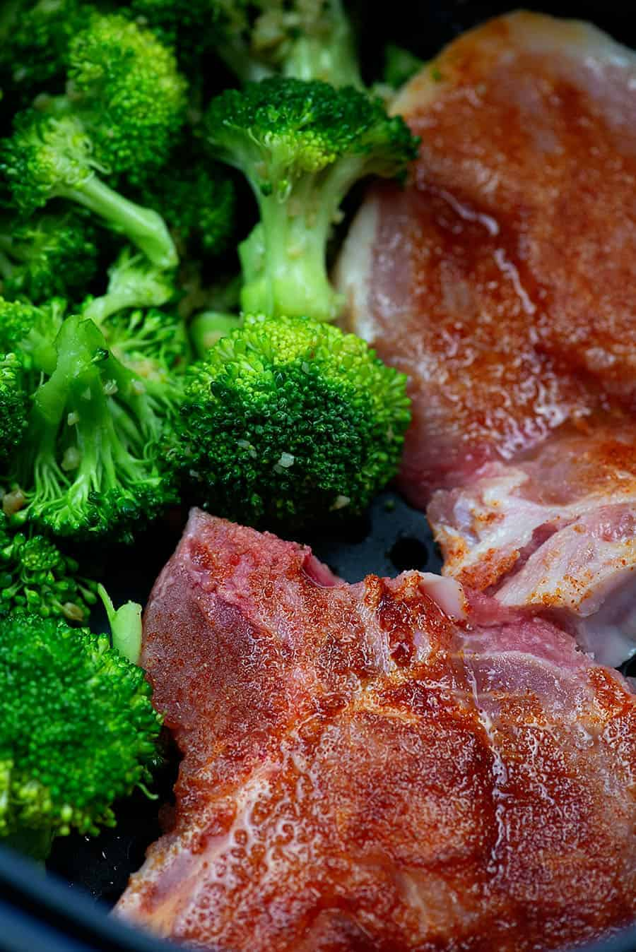 raw pork chops and broccoli in an air fryer basket