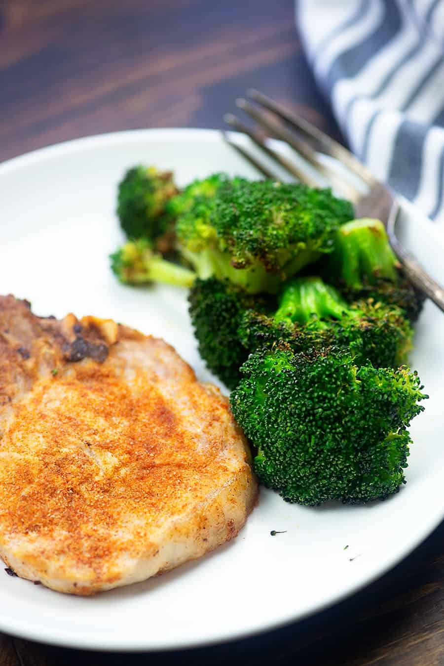 pork chops and broccoli on a white plate with a fork