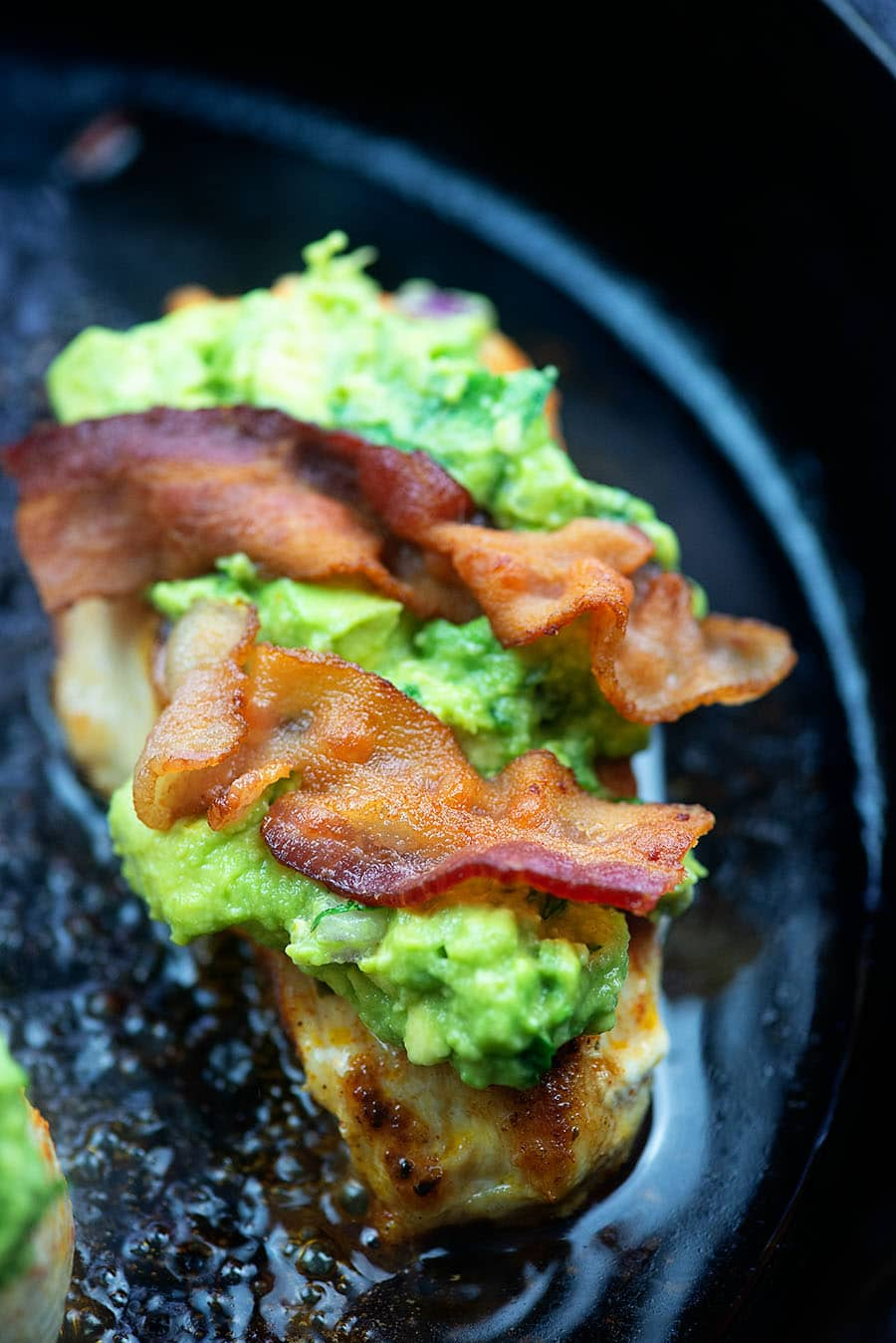 chicken frying in a cast iron skillet topped with guacamole and bacon