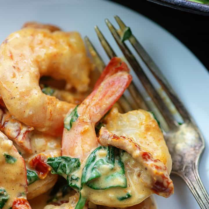 A close up of Tuscan shrimp on a white plate next to a fork.