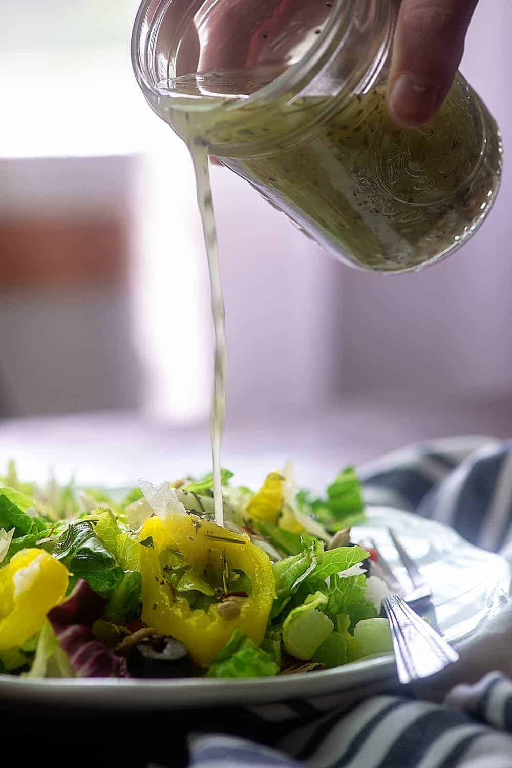 homemade Italian dressing being poured out of a jar onto a salad