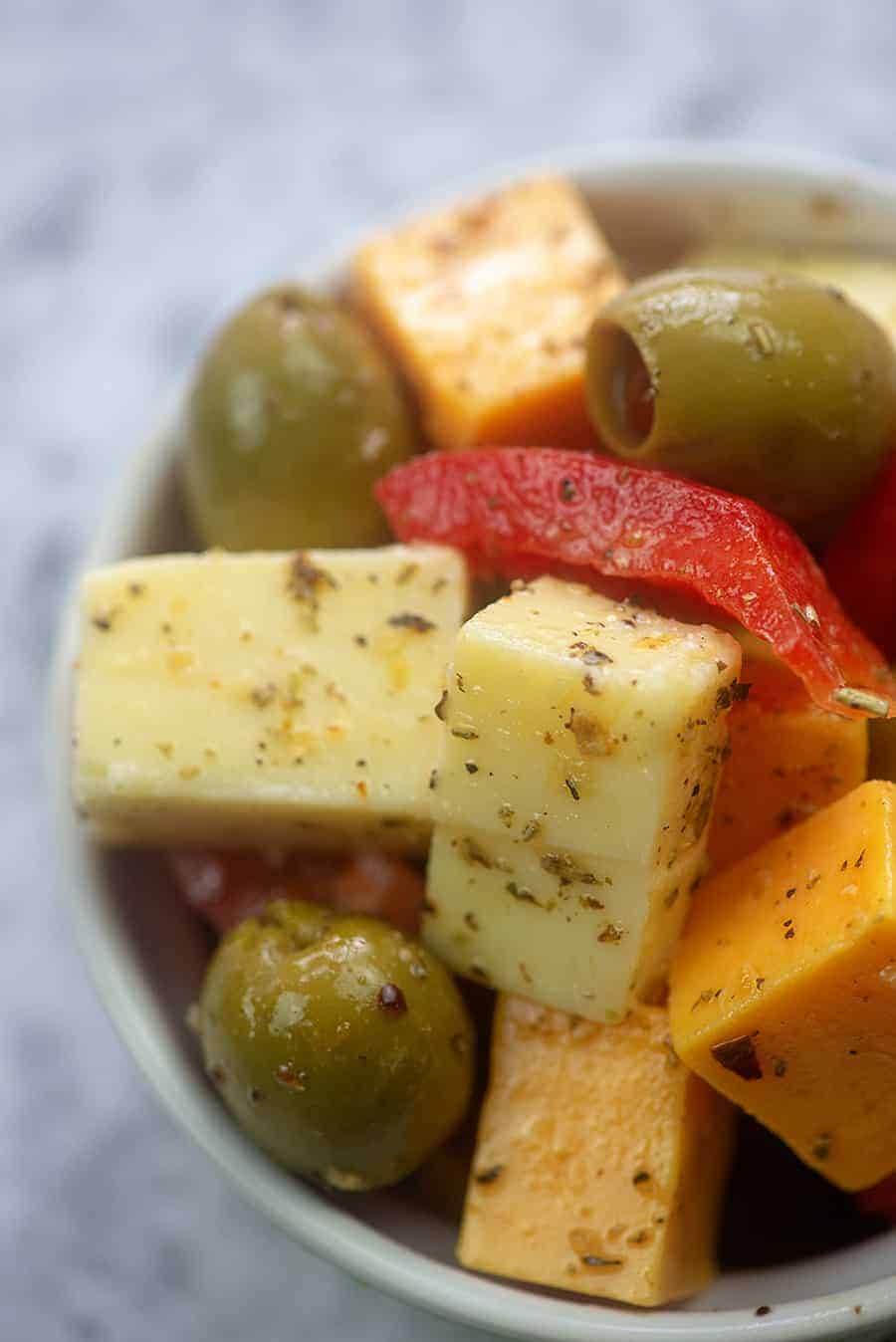 A close up of a bowl of cheese and olives