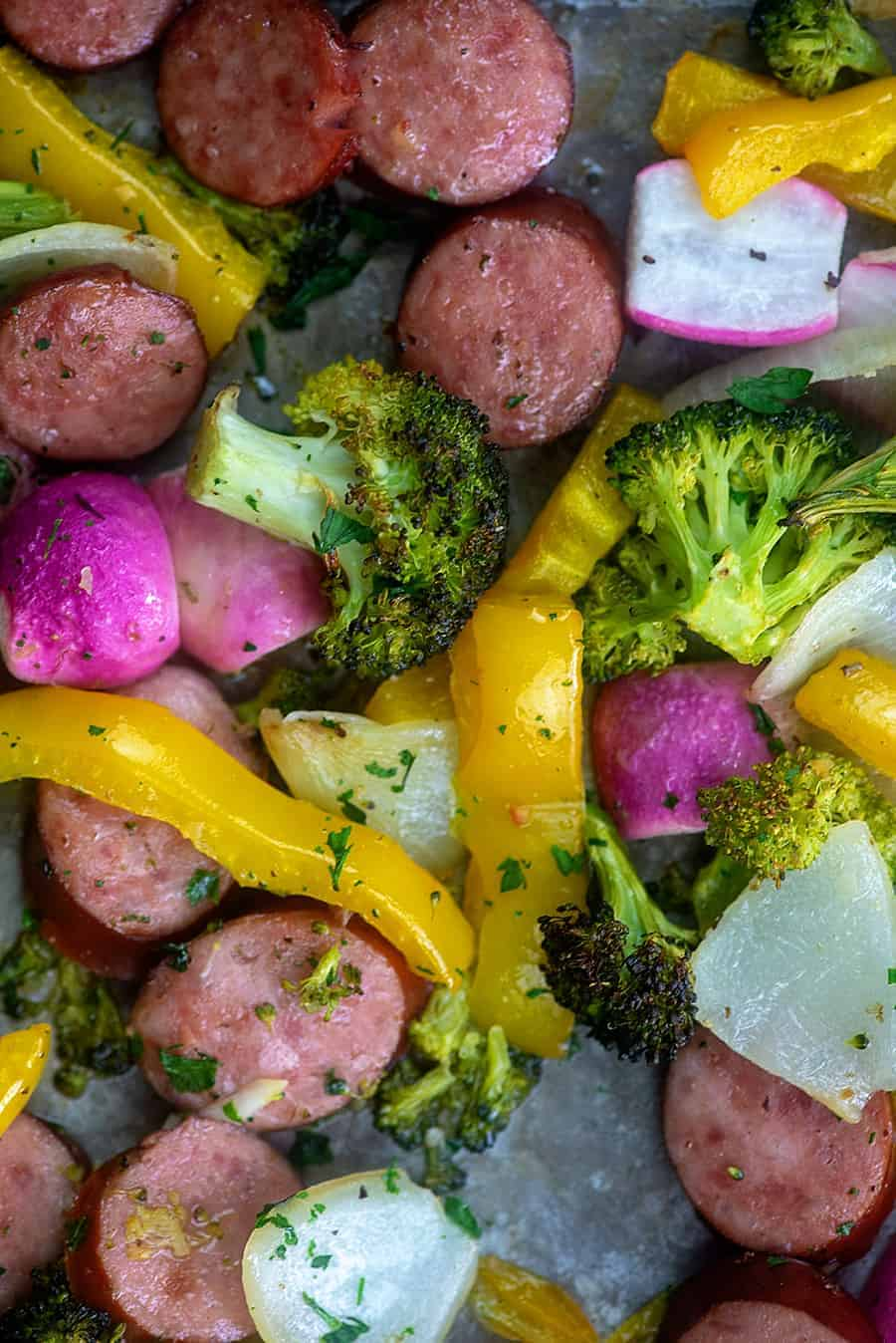 A close up of various vegetables and smoked sausages.