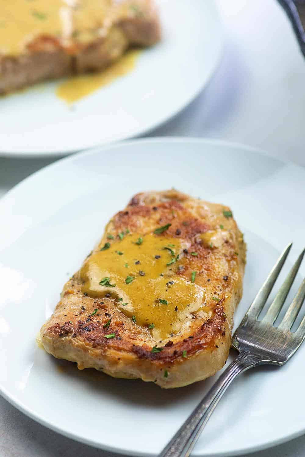 pork chop covered in creamy Dijon sauce on a white plate