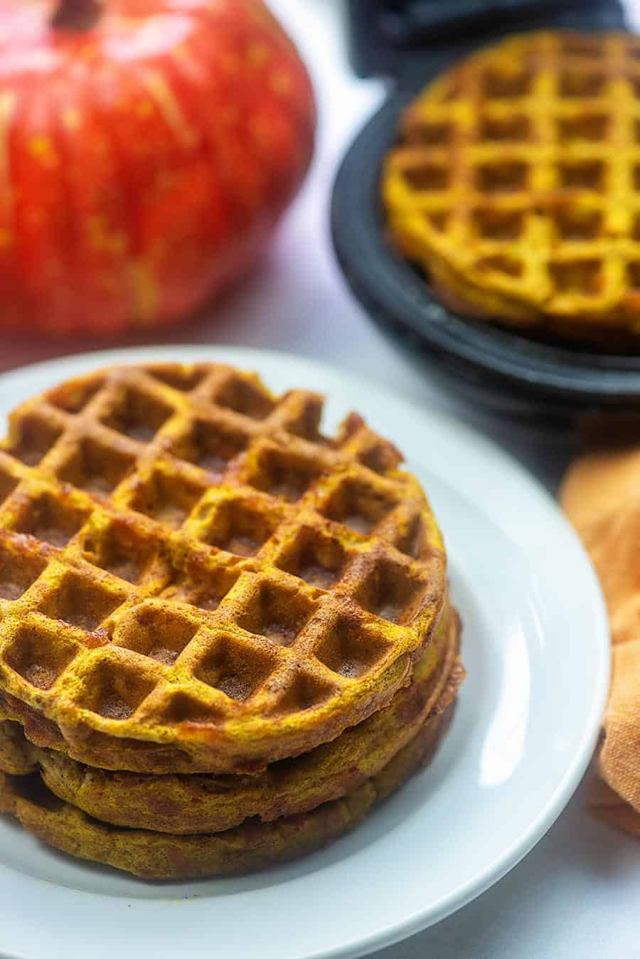 three pumpkin chaffles stacked on a white plate