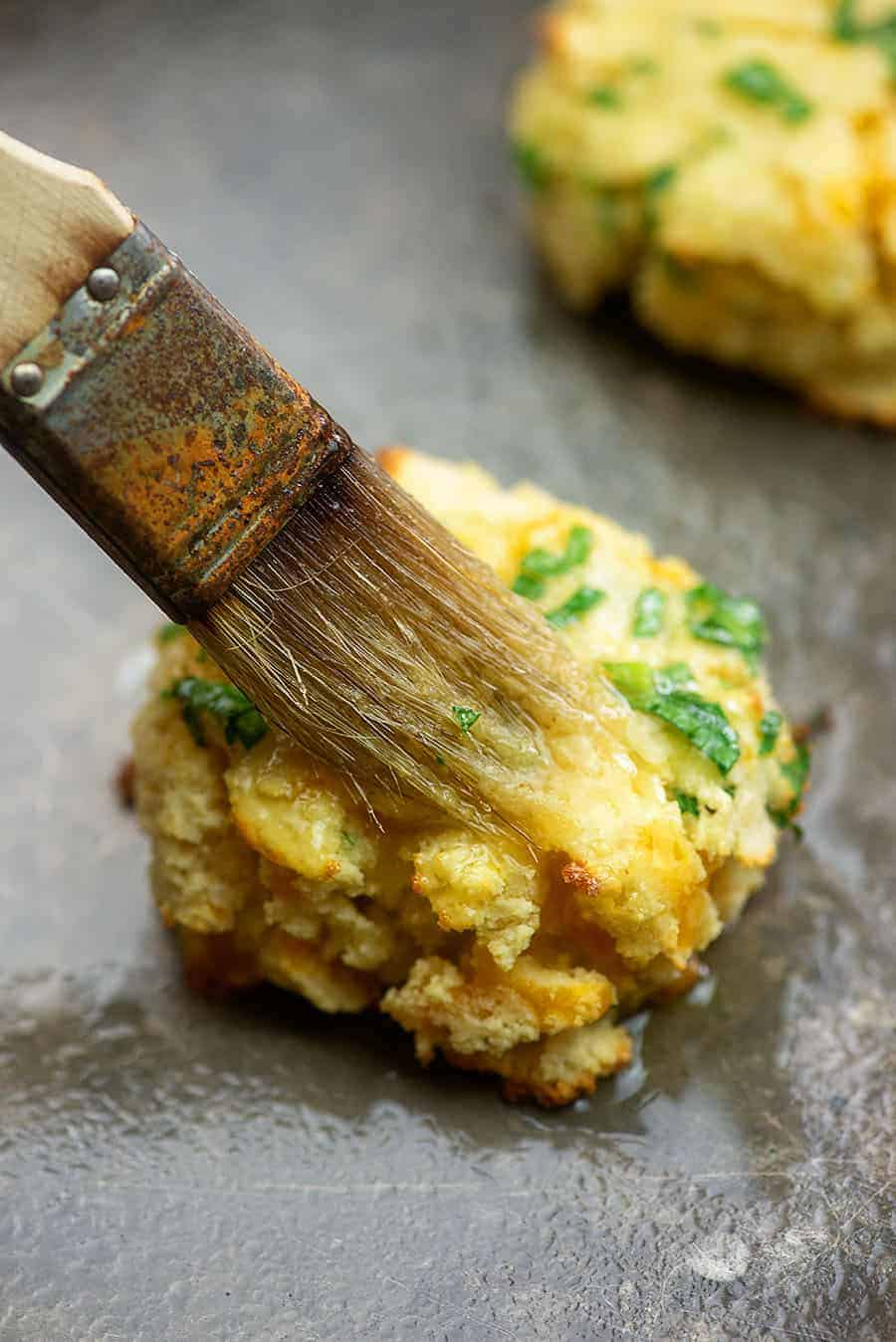 brushing butter on a cheddar biscuit