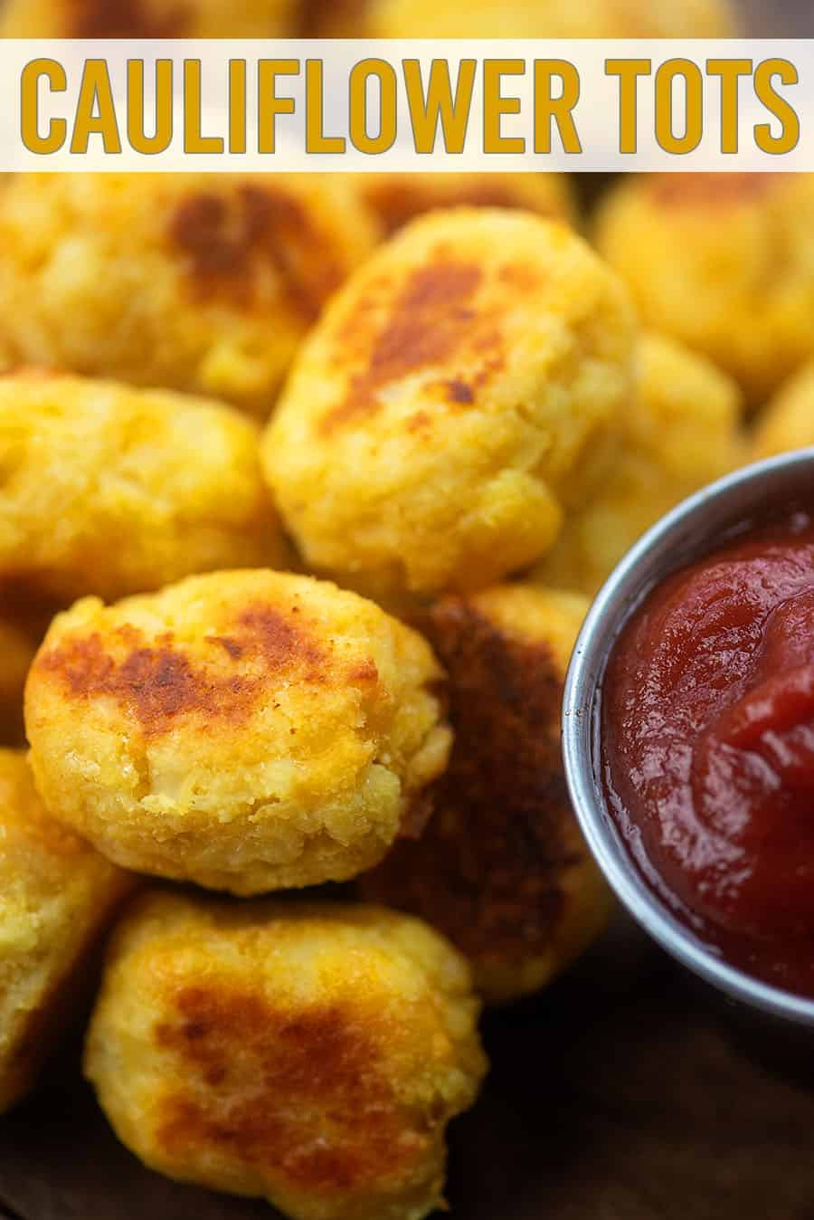 A close up of cauliflower tots piled up next to a cup of ketchup