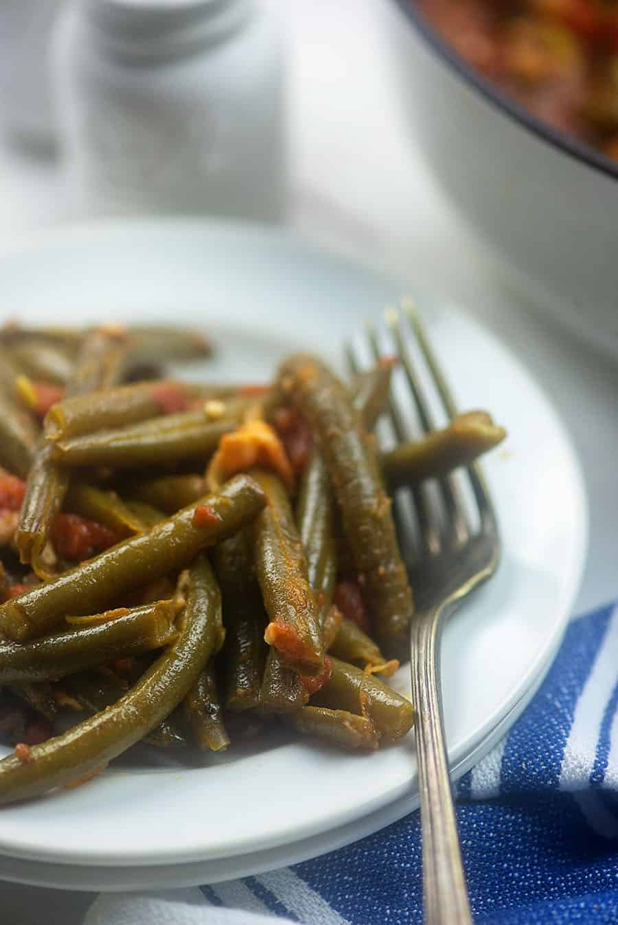 A close up of green beans and a fork on a white plate.