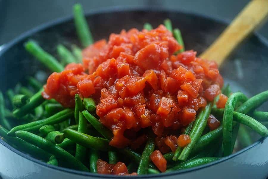 fresh green beans and tomatoes in skillet