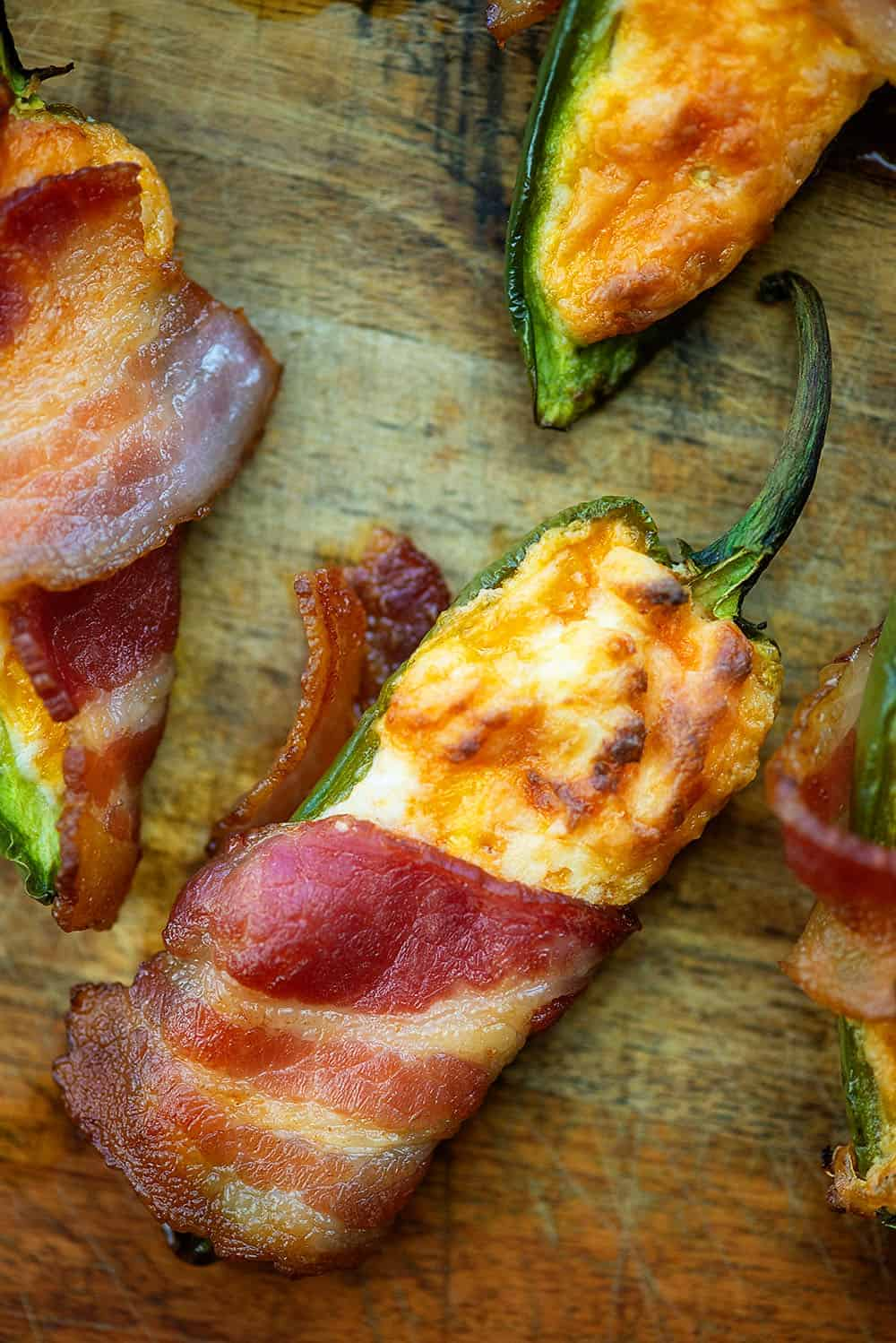 keto jalapeno poppers wrapped in bacon on a cutting board