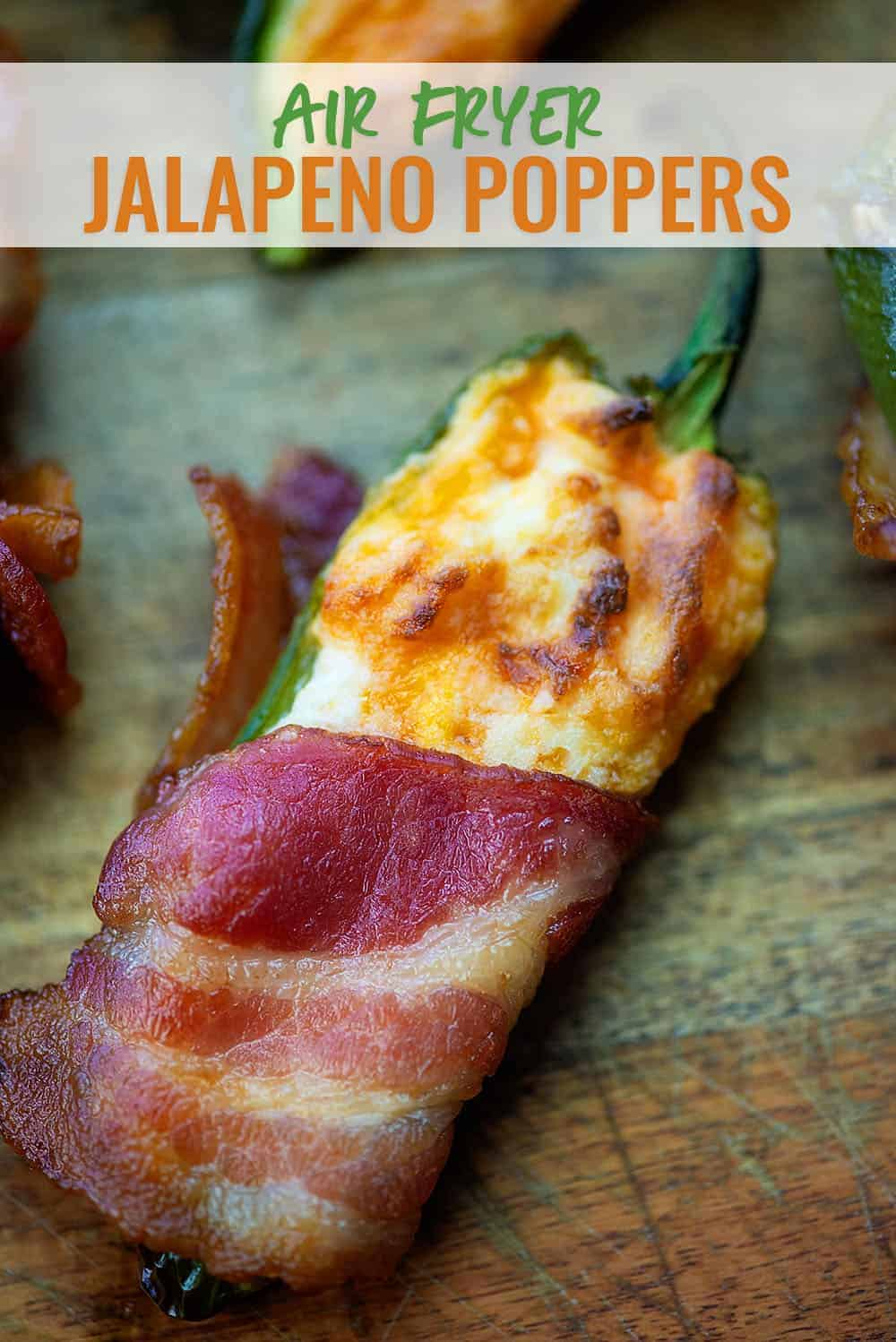 Air Fryer Jalapeno Poppers wrapped in bacon on a cutting board