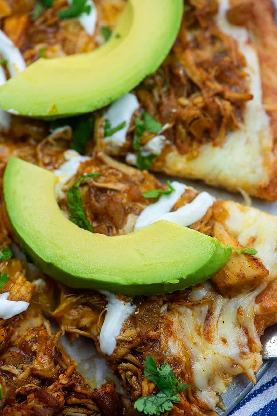 cut up enchilada pizza with avocado slices on every piece