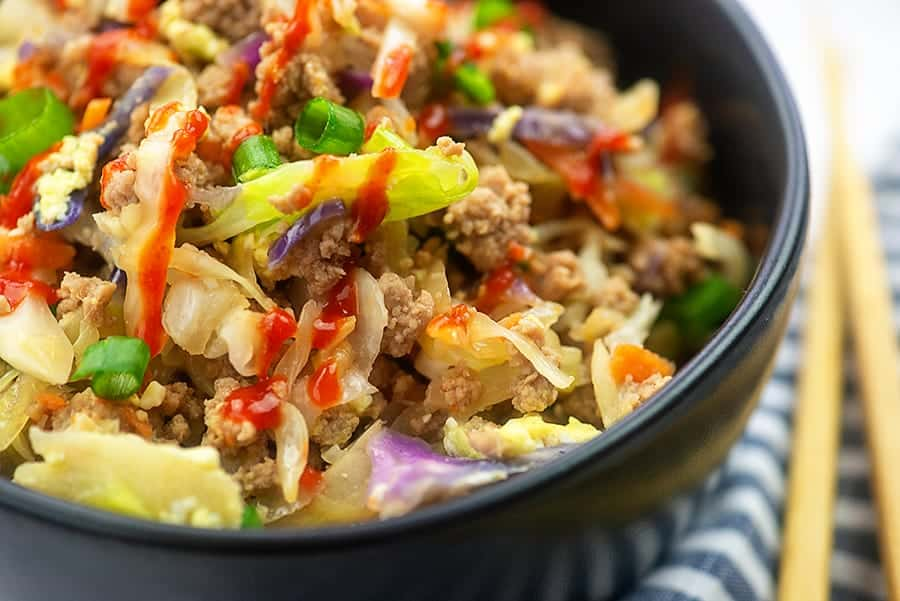 close up of egg roll filling in a black bowl
