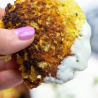 A woman holding up a cauliflower fritter that was dipped in ranch