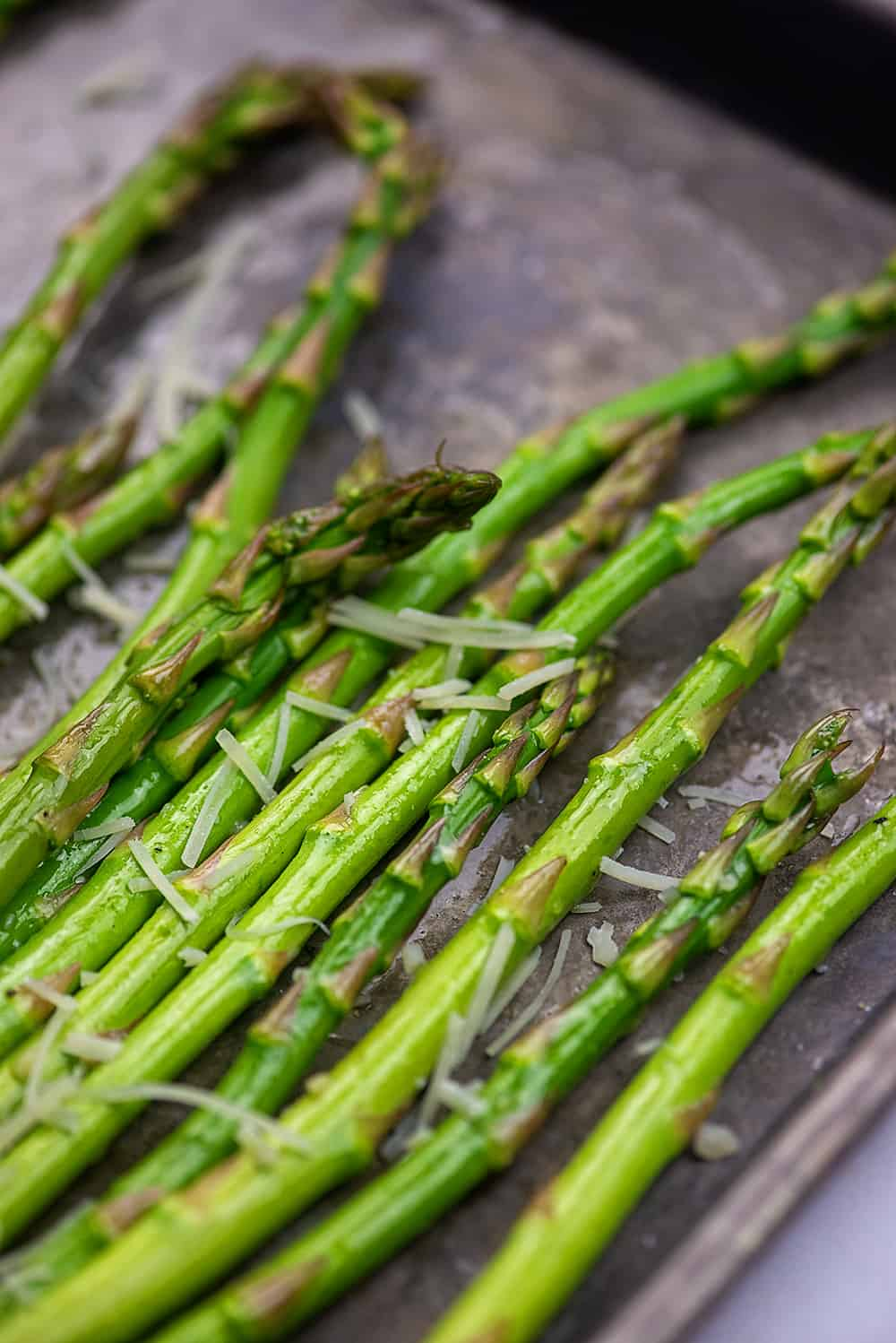 asparagus on baking sheet with garlic and parmesan