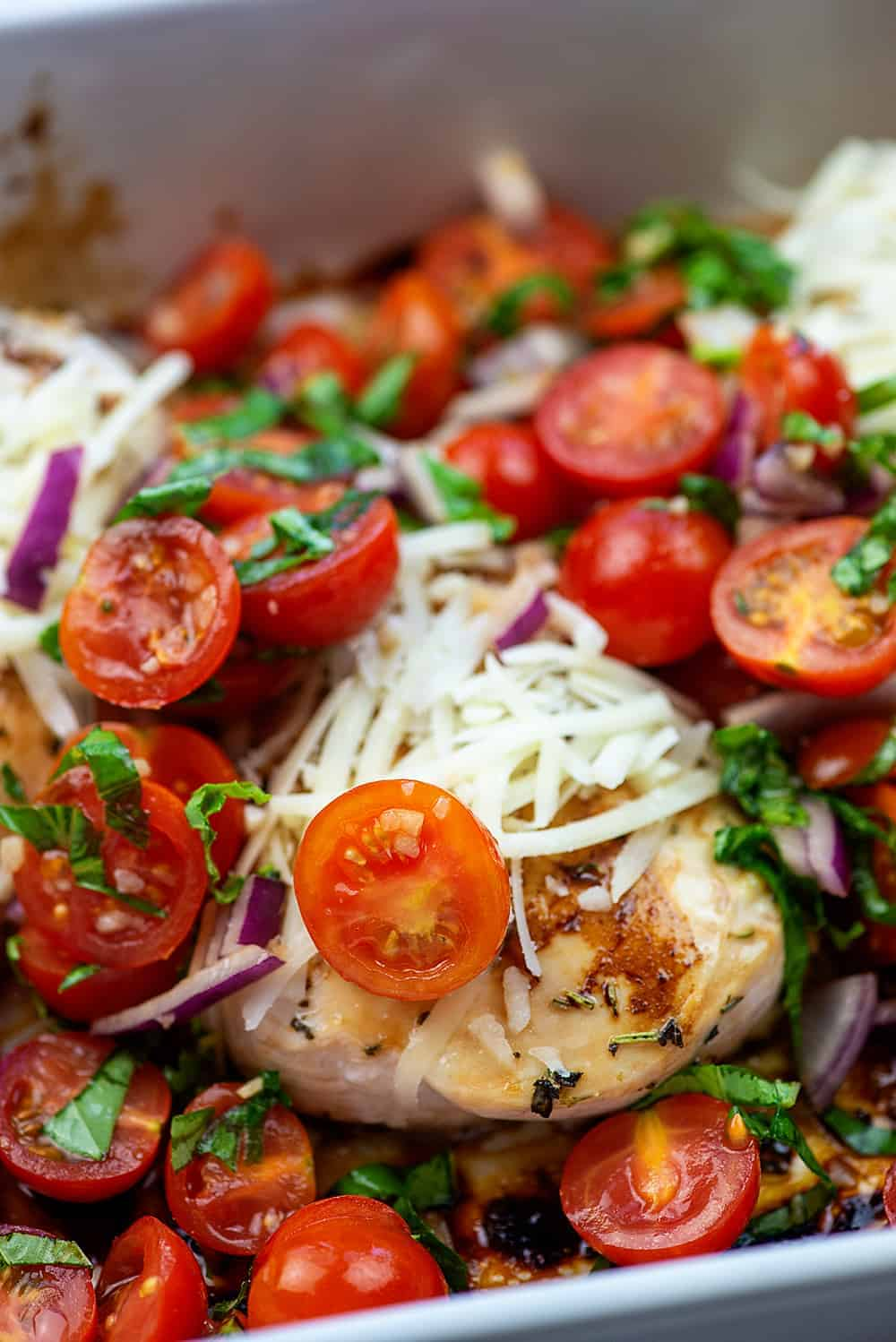 baked chicken with cheese and tomatoes on top