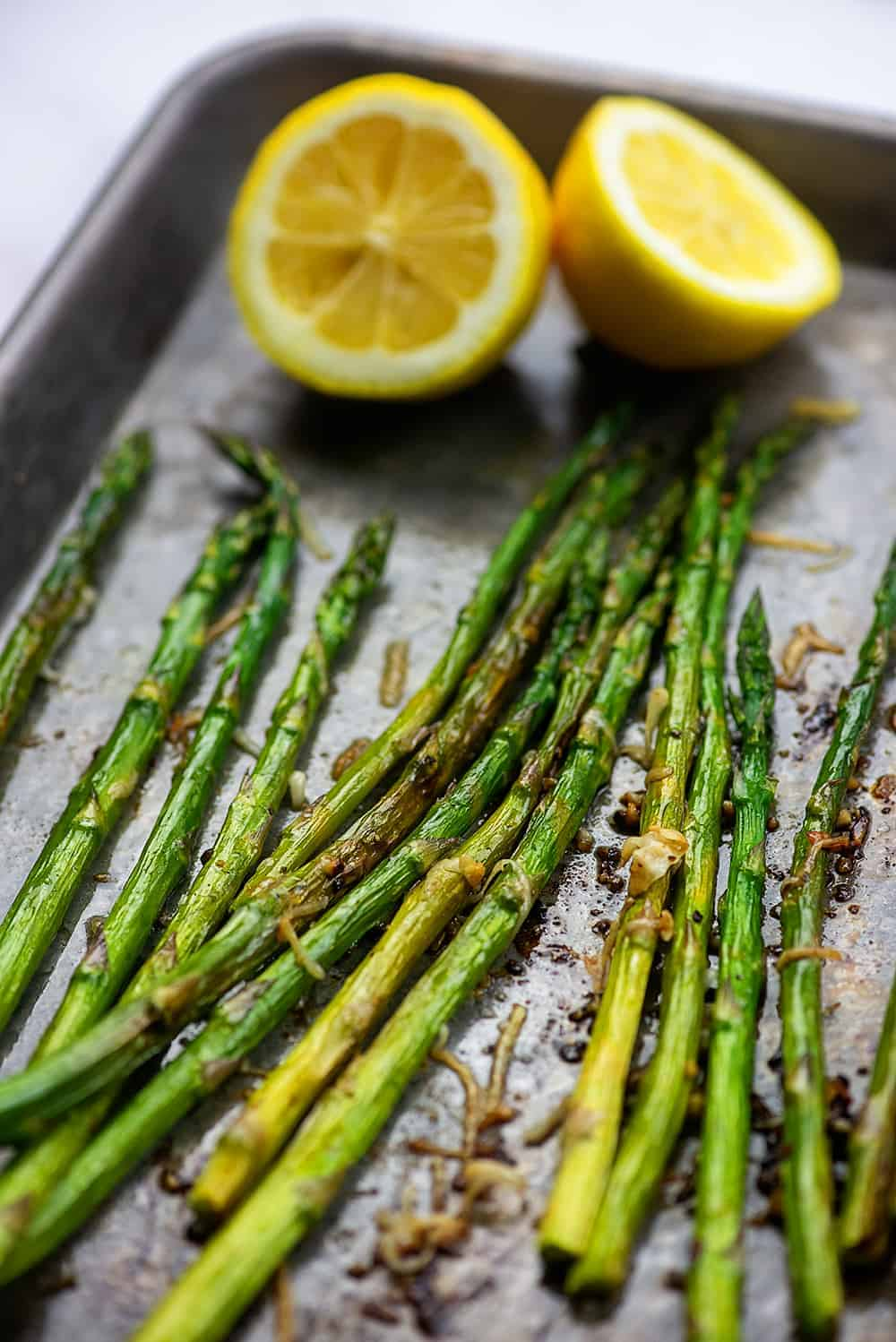 oven roasted asparagus with lemons on baking sheet