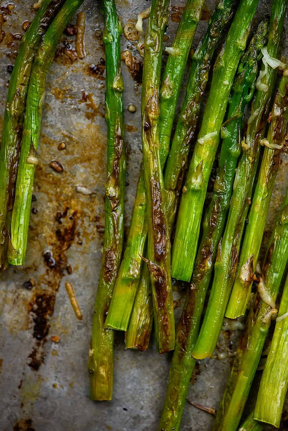 browned asparagus on baking sheet with garlic and parmesan