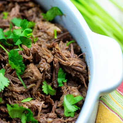 slow cooker shredded beef with cilantro in white dish