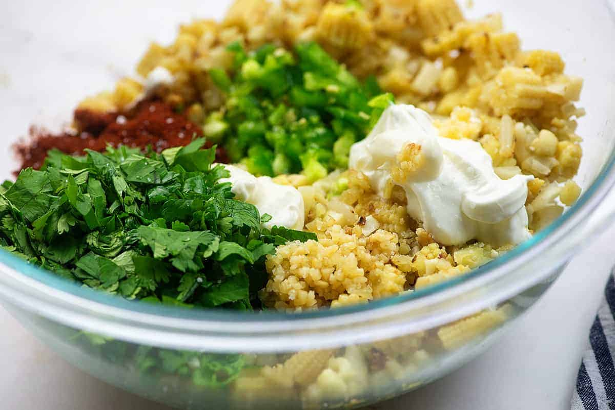 ingredients for low carb mexican street corn salad in glass mixing bowl