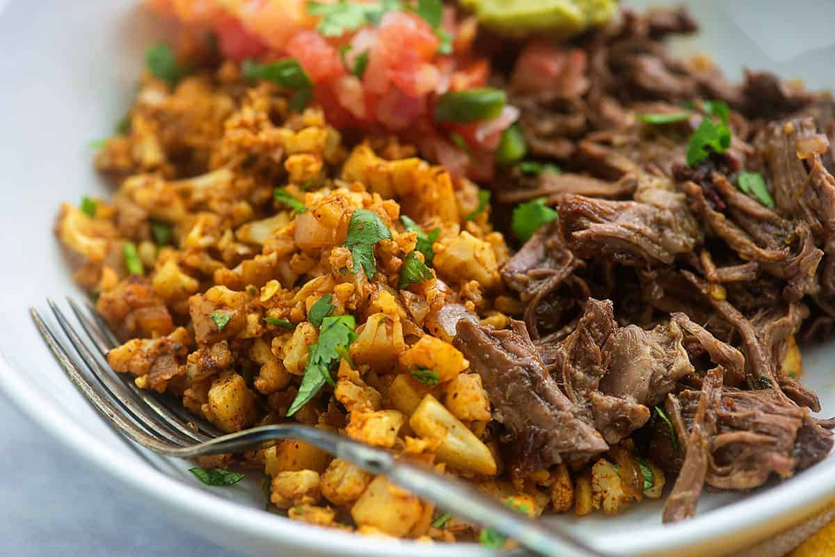 mexican cauliflower rice with barbacoa in white bowl
