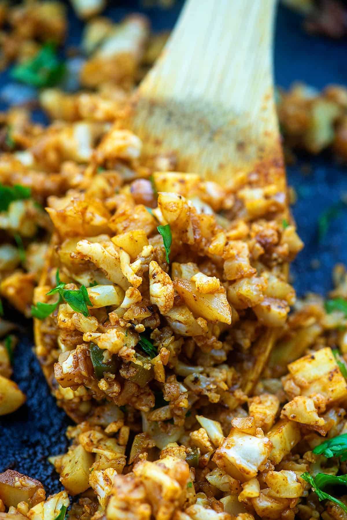 cauliflower mexican rice in skillet on wooden spoon